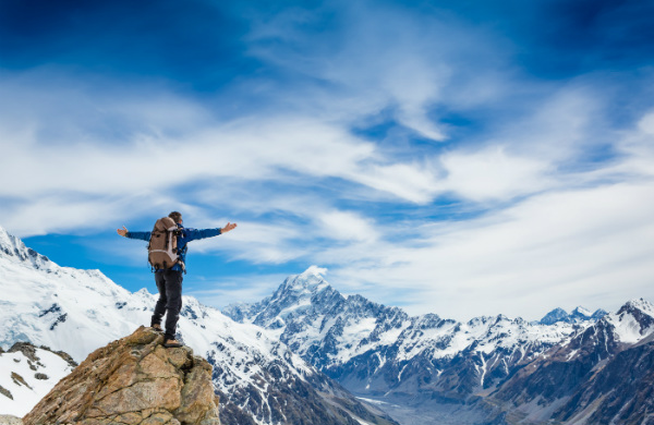 A man celebrates reaching the peak and overcoming the obstacles to behavior change.