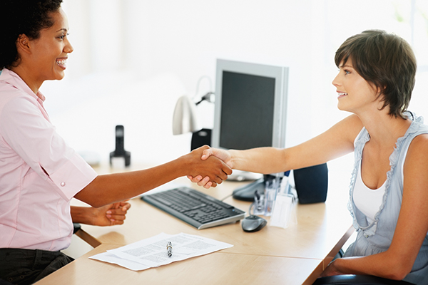 two, female, business people, multicultural, smiling, greeting, handshake, computer, paper, indoors, office, human resources, sales, organization, talent, sales person, portrait, deal closing, application, job interview, hiring,